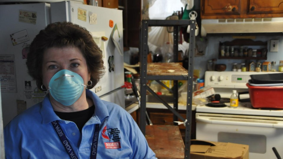 Disaster response coordinator in mask, in ruined home