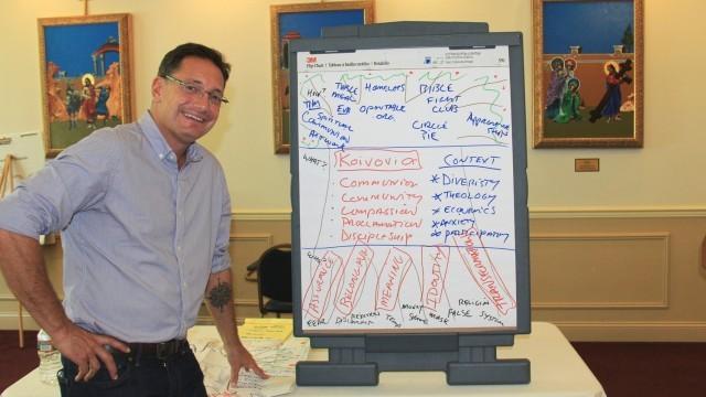 Rev. Jim Walker standing next to whiteboard diagram