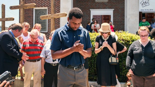Robert Griggs prays with others outside Morris Brown AME Church in Charleston, SC