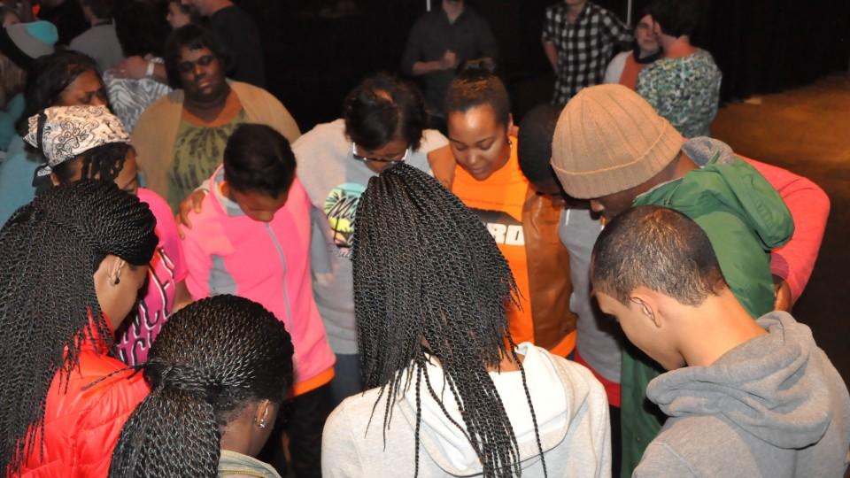 Youth praying in circle during altar call
