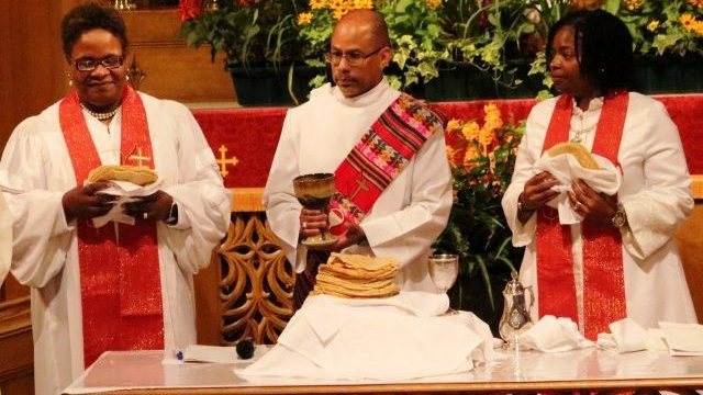 The Rev. David W. Brown, Deacon, (center) joins newly elected Bishops LaTrelle Miller Easterling (left) and Cynthia Moore-Koikoi in serving Communion during their consecration service at First UMC Lancaster July 15, at the close of the NEJ Conference.