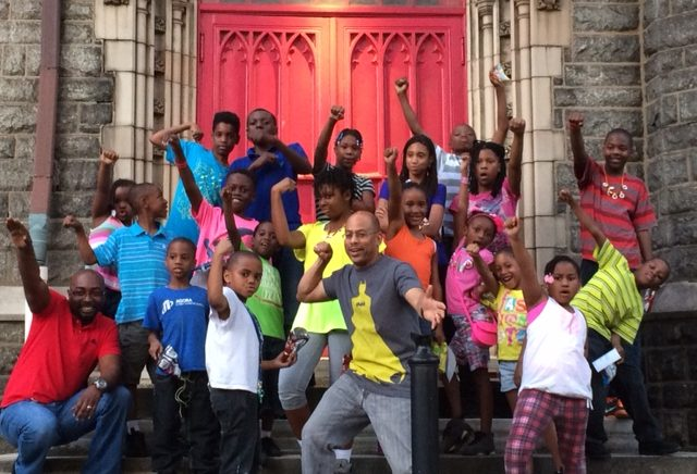 "Pictured at Wharton-Wesley United Methodist Church are Senior Pastor Rev. Eric W. Carr, Jr., (far left front row in red shirt) and the Rev. David W. Brown, Deacon (center in gray ""Batman"" shirt) as they strike a superhero pose with neighborhood children with whom they work in their community ministry there."